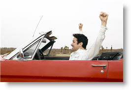 Man in classic red convertible with both arms raised high with delight